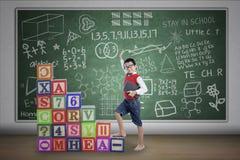 Asian boy step on crossword in class. Asian student boy stepping on crossword in class stock photo