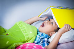 Asian boy surprised, child covering head with book. Stock Photos