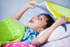 Asian boy surprised, child covering head with book. Royalty Free Stock Photo