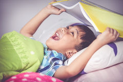 Asian boy surprised, child covering head with book. Vintage tone Royalty Free Stock Images