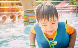 Asian boy swimming with life jacket. In pool Stock Photo