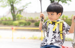 Asian boy swinging in playground with bright Stock Photography