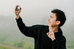 Asian boy teenager wearing black winter clothing Stand to take pictures of yourself with a mobile phone On the road along the. Reservoir in the morning mist And stock image