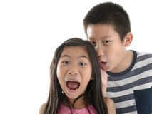 Asian boy telling girl a secret on white Stock Images