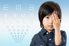 Asian boy testing vision with chart. Close up conceptual portrait of little Asian child testing vision with chart.Boy closing one eye with hand and symbol test Stock Photos