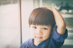 Asian boy is touching his head and hair royalty free stock images