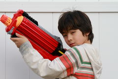 Asian boy with a toy gun. Asian boy pretends to be a gangster with a nerf gun Stock Photos