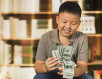 Asian boy with U.S . dollar bank notes Royalty Free Stock Photo