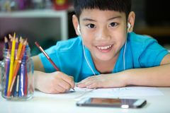 Asian boy using cellphone and painting on a white paper Stock Images