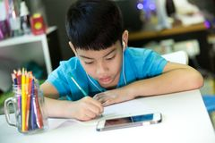 Asian boy using cellphone and painting on a white paper Royalty Free Stock Photos