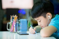 Asian boy using cellphone and painting on a white paper Royalty Free Stock Images