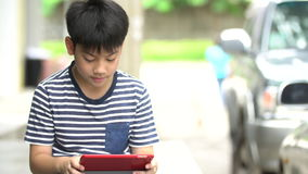 Asian boy using smart cell phone near the road stock video footage