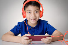 Asian boy ware headphone and playing the cell phone Royalty Free Stock Photography