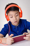 Asian boy ware headphone and playing the cell phone Royalty Free Stock Images