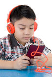 Asian boy ware headphone and playing the cell phone Stock Photography