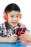 Asian boy ware headphone and playing the cell phone Stock Photo