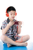 Asian boy ware headphone and playing the cell phone Stock Image