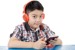 Asian boy ware headphone and playing the cell phone Royalty Free Stock Image