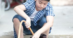 Asian boy washing boot by water tube at home. Asian boy is washing boot by water tube at home stock video footage