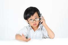 Asian boy wearing glasses making phone call Royalty Free Stock Photos