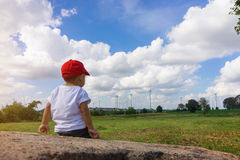 Asian boy wearing a red hat sit and looking at Many wind turbine Royalty Free Stock Photo