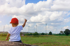 Asian boy wearing a red hat sit and looking at Many wind turbine Royalty Free Stock Photography