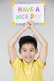 Asian boy with white board with word HAVE A NICE DAY Royalty Free Stock Image