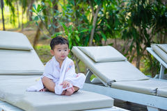 Asian boy with white towel resting on a lounge deck chair or sun. Lounger near swimming pool with big tree and sun light. on summer holidays stock photography