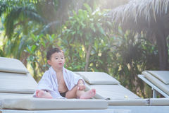 Asian boy with white towel resting on a lounge deck chair or sun. Lounger near swimming pool with big tree and sun light. on summer holidays royalty free stock photography