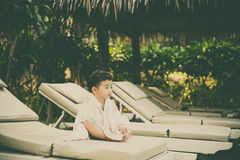 Asian boy with white towel resting on a lounge deck chair or sun. Lounger near swimming pool with big tree and sun light. on summer holidays. vintage tone with royalty free stock photography