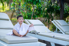 Asian boy with white towel resting on a lounge deck chair or sun. Lounger near swimming pool with big tree and sun light. on summer holidays stock photos
