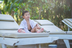 Asian boy with white towel resting on a lounge deck chair or sun. Lounger near swimming pool with big tree and sun light. on summer holidays stock photo