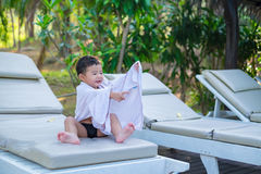 Asian boy with white towel resting on a lounge deck chair or sun. Lounger near swimming pool with big tree and sun light. on summer holidays stock image
