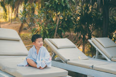 Asian boy with white towel resting on a lounge deck chair or sun. Lounger near swimming pool with big tree and sun light. on summer holidays. vintage tone with stock photography
