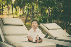 Asian boy with white towel resting on a lounge deck chair or sun. Lounger near swimming pool with big tree and sun light. on summer holidays. vintage tone with stock photos