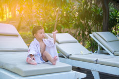 Asian boy with white towel resting on a lounge deck chair or sun. Lounger near swimming pool with big tree and sun light. on summer holidays. soft tone royalty free stock photography