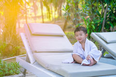Asian boy with white towel resting on a lounge deck chair or sun. Lounger near swimming pool with big tree and sun light. on summer holidays. soft tone stock photos