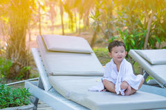 Asian boy with white towel resting on a lounge deck chair or sun. Lounger near swimming pool with big tree and sun light. on summer holidays. soft tone stock images