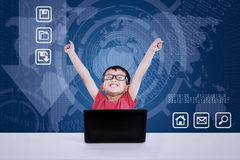 Asian boy winning using laptop on blue background. Asian boy winning using laptop on blue world map background Stock Images