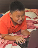 Asian boy working on a laptop computer Stock Image