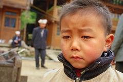 Asian boy 8 years old, is crying in village street. Royalty Free Stock Photo