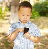 Asian boy 6 years old with a mobile phone in a park Royalty Free Stock Photography
