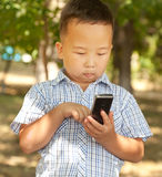 Asian boy 6 years old with a mobile phone in a park. Asian boy 6 years old with a mobile phone Stock Photography