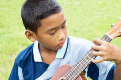 Asian boy. Young boy playing guitar intently Stock Images
