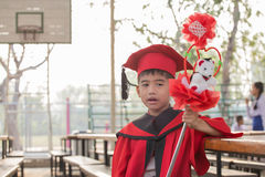 Asian boys face frowning Red graduation gown. In school Royalty Free Stock Photo