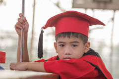 Asian boys face frowning Red graduation gown. In school Royalty Free Stock Image