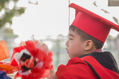 Asian boys face frowning Red graduation gown. In school Stock Photos