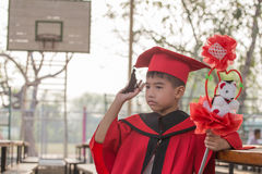 Asian boys face frowning Red graduation gown. In school Stock Photography