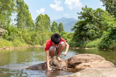 Asian boy looking at fish in a stream.Asian boys are feeding the fish in the stream. stock photo