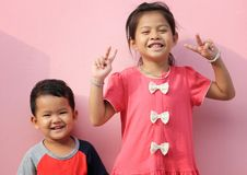 Asian boys and girls in smiling on pink wall background. Royalty Free Stock Images